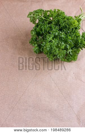 Bunch of parsley and wrapping paper on black wooden background. Copy-space composition