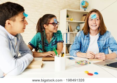Group of children playing guessing game at table in classroom with names on their heads