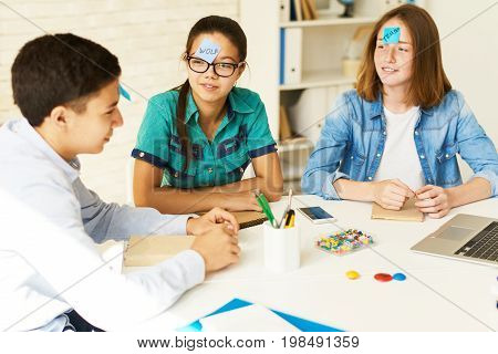 Group of teenagers playing guessing game at table in classroom with names on stickie notes
