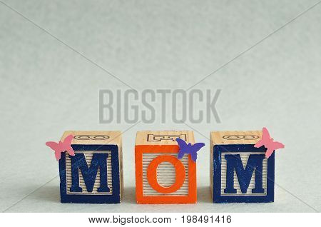 Mom spelled with alphabet blocks and small butterflies