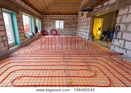 Pipefitter installing system of heating or underfloor heating installation. Water floor heating system interior. Plumbing pipes in apartment during under renovation remodeling and construction.