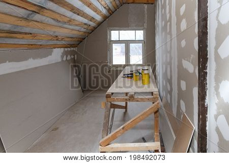 Interior of room apartment with new window and materials (home-made scaffold tools level) during on the renovation overhaul and construction ( remodeling and repairing wall from gypsum plasterboard or drywall and inside roof warming)