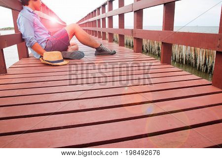 A man in casual clothing sitting alone on wooden bridge Broken heart concept