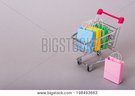 Color packets for purchases in a basket on a gray background. Copy space for text