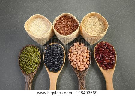 Cereal grains and Seeds beans(Black Bean Red Bean Peanut Mung Bean Thai Jasmine Rice Brown Rice and White Rice) useful for health in wood spoons on grey background.