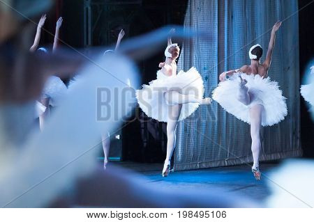 performance, culture, scenery concept. gorgeous ballerinas, wearing costumes of swans for world known ballet, as light as feathers jumping and floating above the stage of the theater