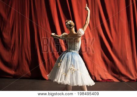 backstage, practice, culture concept. red curtains of theater are still closed and slim ballerina dressed in costume for perfomance with poofy sleeves and flowers in her hair rehearsing her part