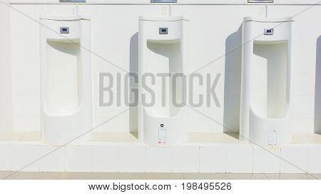 Close up men's white room toilet public toilets