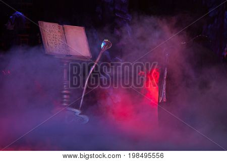 decoration, atmosphere, other world concept. decorating elements for perfomance in mist, grand bookrest, grimoire with some alchemical simbols and magical staff in form of cobra
