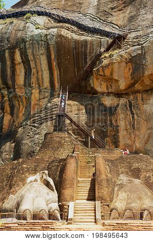 SIGIRIYA, SRI LANKA - MAY 20, 2011: Unidentified tourists climb Sigiriya Lion rock fortress in Sigiriya, Sri Lanka. Sigiriya is listed as UNESCO World Heritage Site.