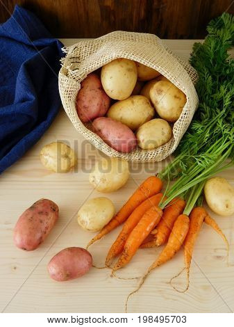 Potatoes in a sack and carrots on a wooden table