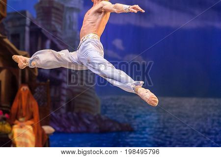 gravity, dance, rehearsal concept. strong caucasian man dressed in silk sky blue pants only like a bird floating above the stage, jumping and doing the splits in the air