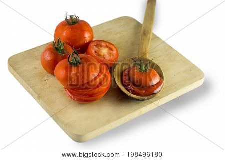 Many wet fresh tomatoes and tomato slice on chopping block with white background.Tomato sauce in wooden spoon and tomato slice on top of sauce   ,Clipping path