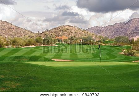 A lush, manicured Arizona golf course with clouds over mountains
