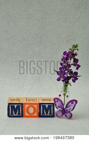 Mom spelled with alphabet blocks and small purple flowers and a silk butterfly