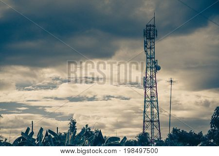 Antenna Of Cellular And Communication System Tower With The Blue Sky And Cloud. Vintage Tone.