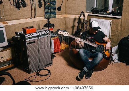 Guitarist in old garage recording studio. Messy music basement with instruments, album making process