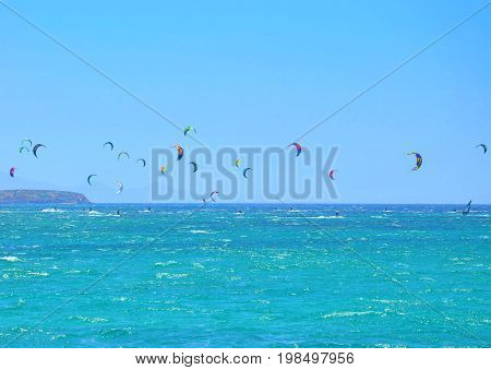 Many kiteboarding kite surfers in the distance near on Punda beach on Paros island