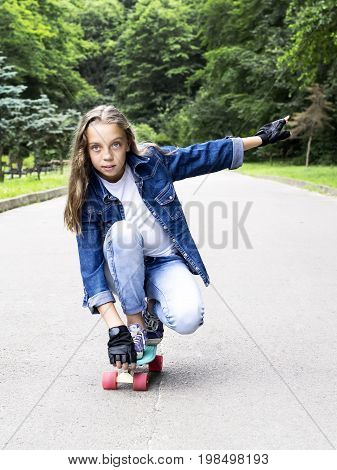 Beautiful blonde teen girl in jeans shirt on skateboard in park on sunny summer day