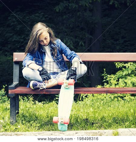 Beautiful blonde teen girl in jeans shirt sitting on bench with backpack and skateboard in park on sunny summer day