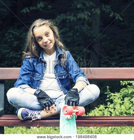 Beautiful blonde teen girl in jeans shirt, sitting on bench with backpack and skateboard in park, on sunny summer day