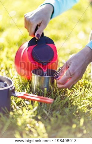 Woman pours water out of kettle in nature