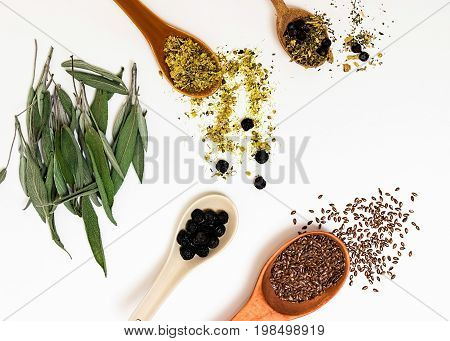Many different medicinal herbs in wooden spoons on a white background isolated. Herbal preparations.