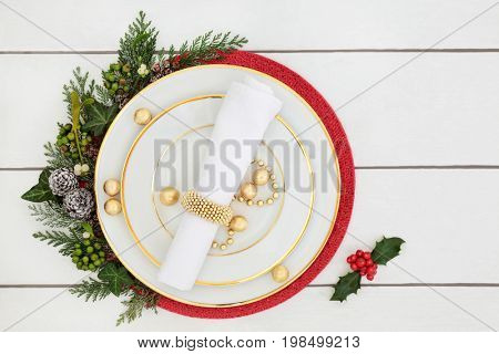 Christmas dinner table setting with porcelain plates, napkin, decorations and foil wrapped chocolates, with holly, mistletoe, ivy and cedar leaves on distressed white wood background