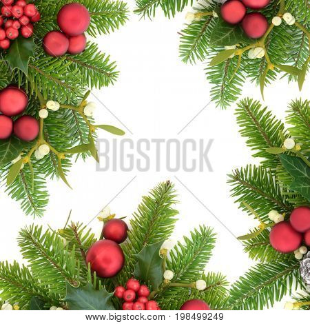 Christmas background border with holly ivy, mistletoe, fir, red bauble decorations and pine cones on white.
