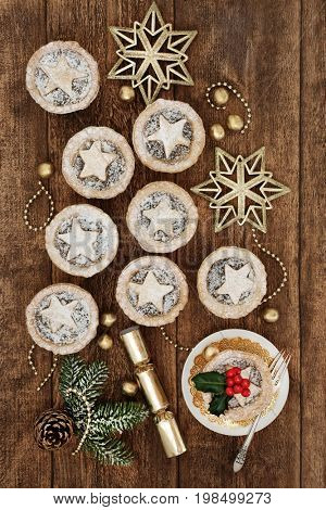 Traditional christmas mince pies with icing sugar dusting, holly, fir and gold bauble decorations on oak wood background.