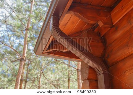 Roof gutter system on log house in forest.