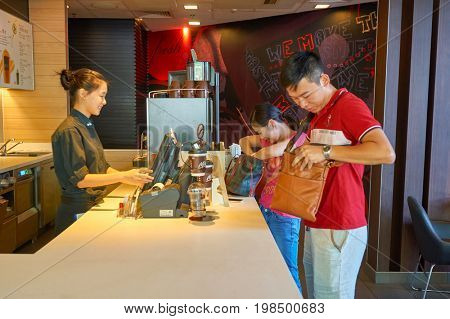 SHENZHEN, CHINA - CIRCA OCTOBER, 2015: people buy coffee at McCafe. McCafe is a coffee house style food and drink chain, owned by McDonald's.