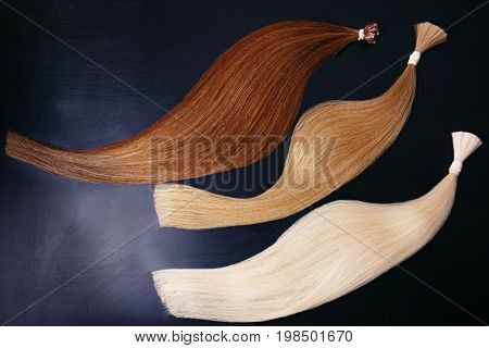 hair extensions of three colors on a dark background