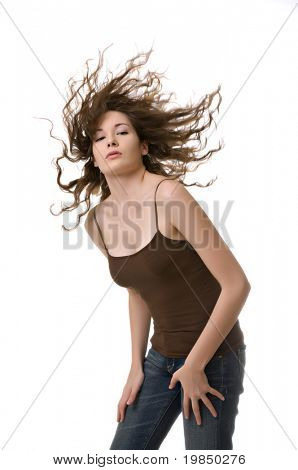 Beautiful young woman tossing her hair isolated against a white background