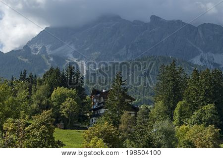 Autumnal corso Italia, the residential district in the town Cortina d'Ampezzo with meadow and mountain, Dolomite, Alps, Veneto, Italy, Europe