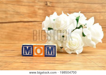 Mom spelled with alphabet blocks and a bunch of white roses