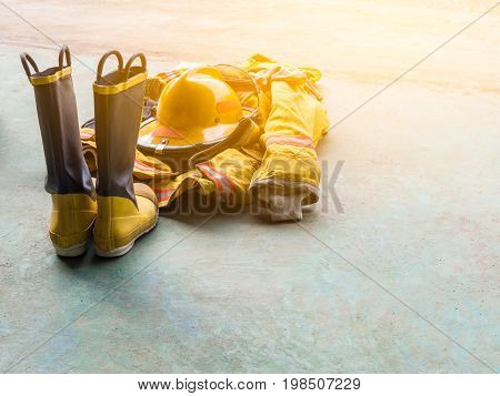 Yellow Fireproof Uniform Of Firefighters. On The Floor. Flare Light.