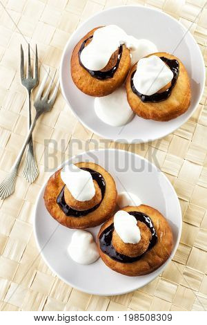 Sweet dessert of beignets with chocolate and cream