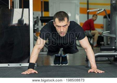 Sportsman Wearing Black Shorts And T-shirt Doing Push-ups