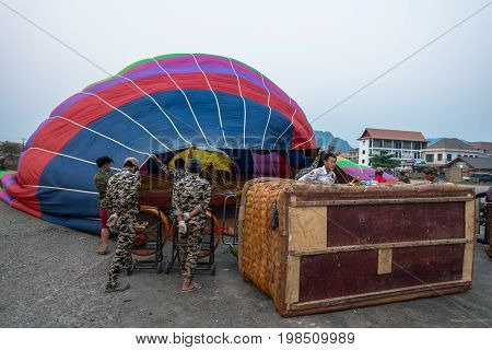 VANG VIENG LAOS - MARCH 15 2017: From back local lao people preparing the balloon before the sunrise in Vang Vieng Laos.