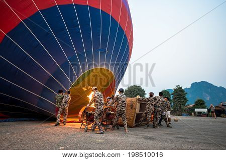 VANG VIENG LAOS - MARCH 15 2017: Horizontal picture of people using fire to heat the air inside the balloon before the sunrise in Vang Vieng Laos.