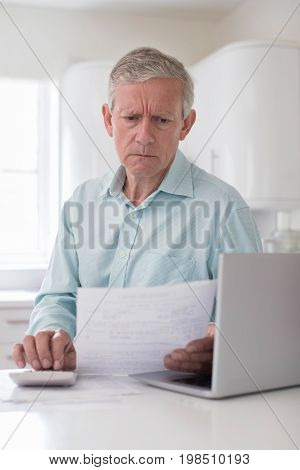 Worried Mature Man With Laptop Calculating Household Finances