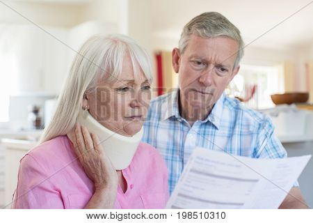 Mature Couple Reading Letter About Wife's Injury