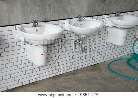 Faucet and white sink in a public toilet.