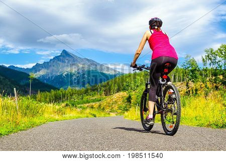 Woman on MTB bike on road in Ticha valley at High Tatras mountains Slovakia.