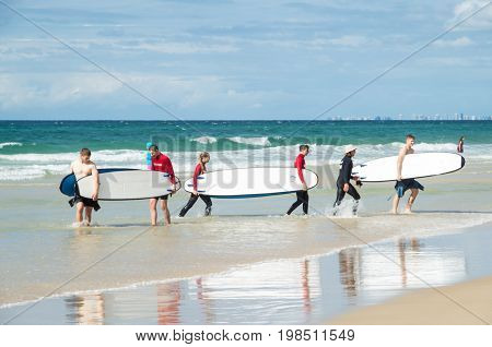 Gold Coast, Australia - July 11, 2017: young surfers carrying their surfboards across the beach at Surfers Paradise.