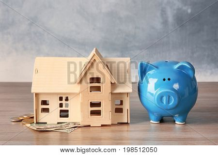 Piggy bank with money and house model on table. Savings concept