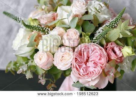 Spring bouquet of white lilacs in vintage gray enamel vase, white wall background behind. luxury wedding bouquet made by a professional florist