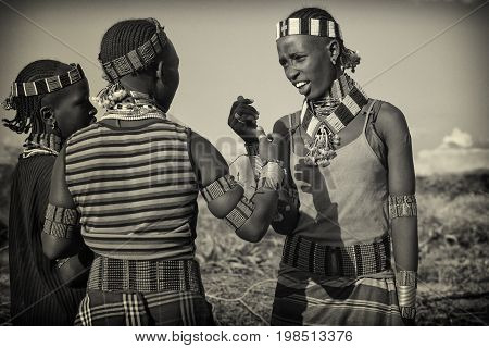 TURMI, ETHIOPIA - NOVEMBER 18, 2014: Young Hamer girls with traditional jewellery and hairstyle in the last light of a day on November 18, 2014 in Turmi, Ethiopia