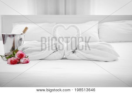 Composition of two towel swans, flowers and ice bucket with champagne on bed in hotel room